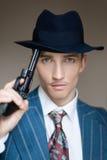 Porträt eines Mörders mit einem Gewehr, das seinen Hut unterstützt Lizenzfreie Stockbilder