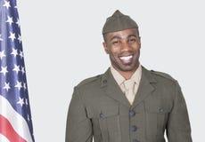 Porträt eines Mann-US-Soldaten, der mit amerikanischer Flagge über grauem Hintergrund lächelt Stockfotos