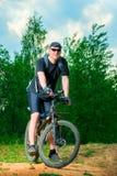 Porträt eines Mannathleten auf einem Fahrrad Lizenzfreie Stockbilder
