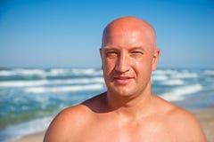 Porträt eines Mannes auf dem Strand des Meeres, gebräunter Körper lizenzfreies stockbild