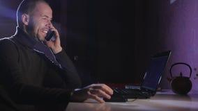 Porträt eines Mannes auf seinem Laptop nachts mit einem Gesicht der Konzentration stock video