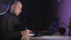 Porträt eines Mannes auf seinem Laptop nachts mit einem Gesicht der Konzentration stock video footage