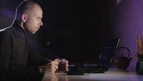 Porträt eines Mannes auf seinem Laptop nachts mit einem Gesicht der Konzentration stock footage