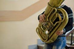 Porträt eines Mannes, der auf der goldenen Tuba spielt lizenzfreie stockfotos