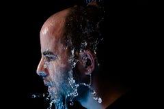 Porträt eines Mannes, der geworfenes Wasser im Gesicht ist Lizenzfreies Stockbild