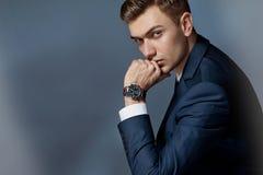 Porträt eines Mannes, der mit einer Klage mit einer Uhr, Studio sitzt Lizenzfreie Stockbilder
