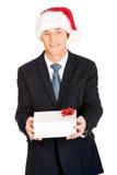 Porträt eines Mannes, der Sankt-Hut hält Geschenk trägt Lizenzfreie Stockfotos