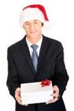 Porträt eines Mannes, der Sankt-Hut hält Geschenk trägt Stockbilder
