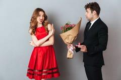Porträt eines Mannes, der zu einem Mädchen mit Blumen vorschlägt Lizenzfreie Stockbilder