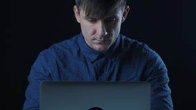 Porträt eines Mannes in einem blauen Hemd, das an einem Laptop in einer Dunkelkammer arbeitet stock footage