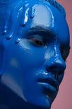 Porträt eines Mannes goss blaue Farbe auf einem rosa Hintergrund Lizenzfreies Stockbild