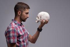 Porträt eines Mannes im Profil mit einem Schädel in seiner Hand Lizenzfreies Stockfoto