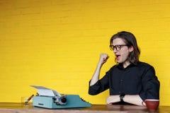 Porträt eines Mannes im schwarzen Hemdglas, Darstellen erfolgreich, gesetzt an einem Tisch nahe Schreibmaschine über gelbem Hinte lizenzfreie stockfotos