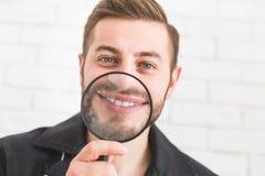 Porträt eines Mannes mit einem Vergrößerungsglas auf einem weißen Hintergrund stockfoto
