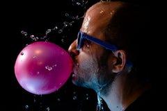 Porträt eines Mannes mit Kaugummi und Sein der Sonnenbrillen geworfenes Wasser im Gesicht Stockfotografie