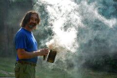 Porträt eines Mannes umgeben durch Rauch gegen das Morgensonnenlicht stockfoto