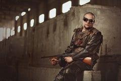 Porträt eines Mannes von der Beitrag-apokalyptischen Welt mit Maschinengewehr und den schwarzen Gläsern in einem verlassenen Gebä Lizenzfreie Stockbilder
