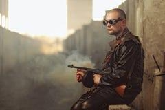 Porträt eines Mannes von der Beitrag-apokalyptischen Welt mit Maschinengewehr und den schwarzen Gläsern in einem verlassenen Gebä Stockbild
