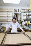 Porträt eines messenden Bilderrahmens des glücklichen jungen Angestellten Stockbild