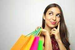 Porträt eines modernen herrlichen Brunette mit dem Taschenkäufer in ihrer Hand was denkend zu kaufen und zur Seite das Kopien-SP  stockfotografie
