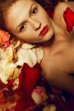 Porträt eines modernen rothaarigen Modells in den rosafarbenen Blumenblättern Stockfoto