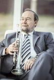 Porträt eines Musikers mit einer Trompete, die in einem Stuhl, auf dem Hintergrund des Konzertsaals sitzt Lizenzfreie Stockfotografie