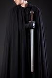 Porträt eines mutigen Kriegerswanderers in einem schwarzen Mantel und in einer Klinge in der Hand lizenzfreies stockfoto