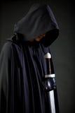 Porträt eines mutigen Kriegerswanderers in einem schwarzen Mantel und in einer Klinge in der Hand lizenzfreies stockbild