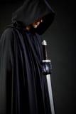 Porträt eines mutigen Kriegerswanderers in einem schwarzen Mantel und in einer Klinge in der Hand stockfotos
