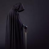 Porträt eines mutigen Kriegerswanderers in einem schwarzen Mantel und in einer Klinge in der Hand lizenzfreie stockfotos