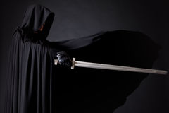 Porträt eines mutigen Kriegerswanderers in einem schwarzen Mantel und in einer Klinge in der Hand lizenzfreie stockfotografie