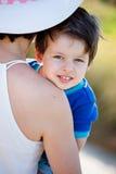 Porträt eines netten Babys auf Mutterhänden Stockfotografie