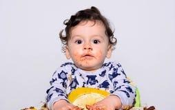 Porträt eines netten Babys, das den Kuchen macht eine Verwirrung isst Fungierendes überraschtes Versuchen des Babys, seins zu ver Stockfotos