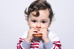 Porträt eines netten Babys, das einen Keks isst Stockfoto