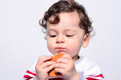 Porträt eines netten Babys, das einen Keks isst Lizenzfreies Stockbild