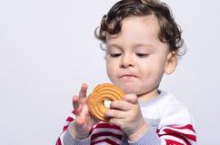 Porträt eines netten Babys, das einen Keks neugierig betrachtet es isst Stockbilder