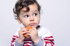 Porträt eines netten Babys, das einen Keks oben schaut neugierig isst Stockbild