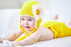 Porträt eines netten Babys im gelben Hut und in den Hosen, die sich auf a hinlegen Lizenzfreie Stockfotografie