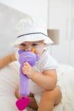 Porträt eines netten Babys mit dem Spielzeug, das auf Bett sitzt Lizenzfreies Stockbild