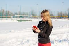 Porträt eines netten blonden Mädchens, das Musik beim Gehen hinunter die Straße in der Hand hält ein rotes Telefon hört Schnee li lizenzfreie stockfotos