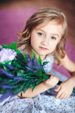 Porträt eines netten blonden Mädchens in einem schönen Kleid mit Blumen in ihren Händen Lizenzfreies Stockfoto
