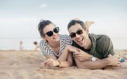 Porträt eines netten, entspannten Paares, das auf Sand legt Stockbilder