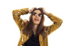Porträt eines netten erstaunlichen Mädchens in einer Jacke des strahlenden Golds und in runden Gläsern Lizenzfreies Stockfoto
