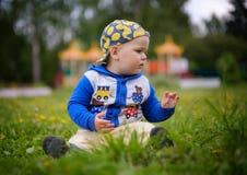 Porträt eines netten europäischen Jungen auf einem grünen Rasen mit Löwenzahn stockbild