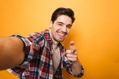 Porträt eines netten jungen Mannes, der ein selfie nimmt Stockfotos