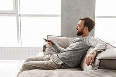 Porträt eines netten jungen Mannes, der Fernsehen Fernsteuerungs hält Lizenzfreie Stockfotos