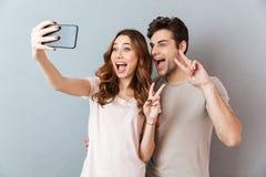 Porträt eines netten jungen Paares, das Frieden zeigt, gestikulieren Lizenzfreies Stockbild