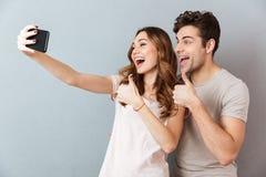 Porträt eines netten jungen Paares, das sich Daumen zeigt Lizenzfreies Stockfoto