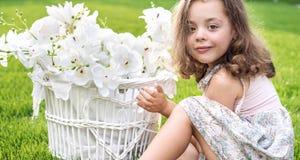 Porträt eines netten Kindes, das einen Weidenkorb mit weißem Fluss hält lizenzfreie stockbilder