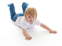 Porträt eines netten kleinen Jungen, der auf Boden liegt Lizenzfreie Stockbilder